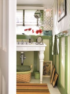 The faux paneling in this bathroom was crafted of 4x4's, and painted in complementary light and dark greens. For rooms (not just bathrooms!) with short ceilings, try placing art on the floor, rather than hanging it on the walls to give the room a sense of added height.    Read more: Decorating with Green - Ideas for Green Rooms and Home Decor - Country Living  Two-Toned Bathroom