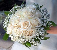 Hand tied bouquet of white roses rimmed with babies breath and ruscus foliage.