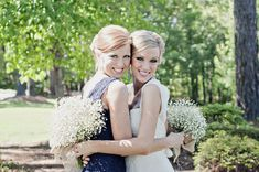 Sister wedding photo! I love the flowers behind their backs!