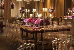 Purple and Gold wedding decoration, with purple and link flower arrangements, candles, acrylic chairs, curtains and purple table