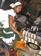 An Ethiopian woman preparing coffee at a traditional ceremony. She roasts, crushes and brews the coffee on the spot.