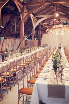 long rectangle tables with burlap runners and flowers down the middle.