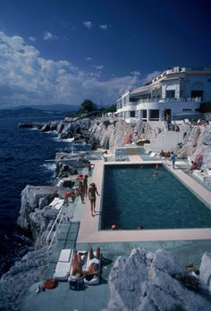 Eden Roc pool | Guests by the pool at the Hotel du Cap Eden-Roc, Antibes, France, August 1976 by Slim Aarons