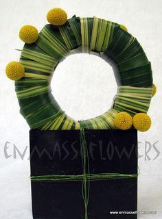 Unusual leaf covered wreath with yellow craspedia embellishment.