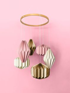 """A stunning hand crafted hanging mobile consisting of six individual geometric shapes folded from specialty stocks. A beautiful wooden """"halo"""" hovers above—complementing the materials below. A unique display worthy of any nursery or child's room. Nursery Room, Nursery Decor, Baby Nest, Hanging Mobile, Kidsroom, Dusty Pink, Geometric Shapes, Baby Shop, Pink And Gold"""