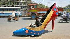 A worker tests a car in the shape of a womans show in Hyderabad, India. The shoe is part of a series by Indian car designer Sudhakar Yadav and it can run at a maximum speed of 28 mph.