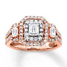 This brilliant 3-stone diamond ring features an emerald-cut diamond encircled with round diamonds set in 14K white gold, flanked on either side by additional emerald-cut diamonds. Additional round diamonds enliven the 14K rose gold band to complete the look. The ring has a total diamond weight of 1 1/2 carats. Diamond Total Carat Weight may range from 1.45 - 1.57 carats.