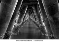 An infinity shot under the concrete bridge of some obscure fishing village in the south pacific. Light creates distinct edging of the diagonal pillars while barnacles cling to the granite surfaces like leeches. The audience can't help but be drawn to the center of the tunnel shaped as an capital a.