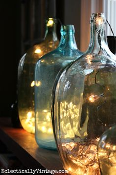 Demijohn bottles filled with string lights for Christmas eclecticallyvintage.com