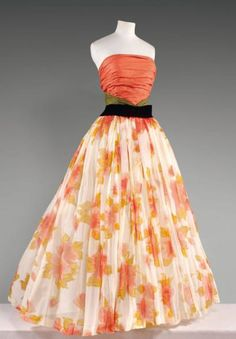 Pierre Balmain, haute couture, No. 108011, circa 1955/1958 Evening dress, strapless top draped gazar coral emphasized gazar green, very full skirt in ivory organza printed with large flowers coral and beige, waist highlighted by a curved belt of black velvet.