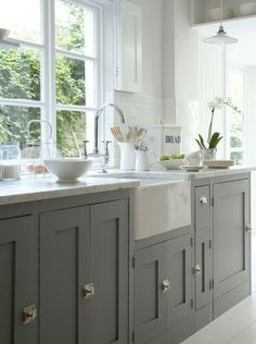 Farmhouse style sink with dark gray shaker style cabinetry. Marble countertops and white subway tile back splash