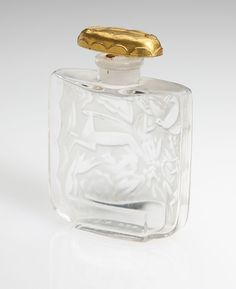Lot# 1010 A French Art Deco gilt and frosted glass 'Monjoly' by Lubin perfume bottle, Chevalier & Viard. Circa 1927, molded ''Lubin - Paris'' and acid stamped ''France'', designed by George Chevalier and Julien Viard, with oval gilt-topped stopper above a rectangular bottle decorated in stylized relief with figures and animals, 2.5'' H x 2'' W x 0.75'' D, est: $300/500 *Price Realized: $720.00