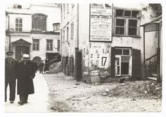Men walking on a path in the shulhoyf. A Yiddish poster advertising the services of shipping agent L. Kopelovitsh to emigrants to Palestine. Election posters. Vilna, Lithuania 1930s.