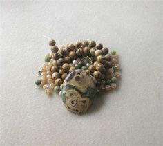 These DIY jewelry kits contain a pendant with coordinating beads and findings so you can easily make a necklace with one stop shopping!    *  brown green jasper oval pendant, top drilled front to back, 35 x 56 x 6mm (dyed)   *  picture jasper round beads, 15 strand, 8mm   *  serpentine round beads, 6mm   *  desert sand glass faceted rondelle beads, 4 x 6mm   *  antiqued brass spacers, 6mm   *  antiqued brass designer toggle clasp, 16mm   Each kit comes with 4 crimp beads and 20 inches of…