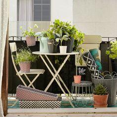 Mały balkon z beżowym składanym stołem i składanym krzesłem. Pokazany z doniczkami w różnych kolorach i rozmiarach i mnóstwem zielonych roślin.