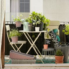 Ein kleiner Balkon mit faltbaren SALTHOLMEN Möbeln, einem Tisch und zwei Stühlen in Beige, und vielen Grünpflanzen in Übertöpfen in unterschiedlichen Größen und Farben