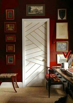 Dark red walls with white trim and doors with geometric brass nailhead trim