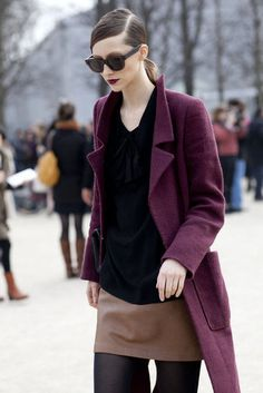 hair slicked into deep side part ponytail with plain black sunglasses and dark lips, plum lip and matching coat, crew neck shift with dark top and thick camel stripe at bottom, black tights