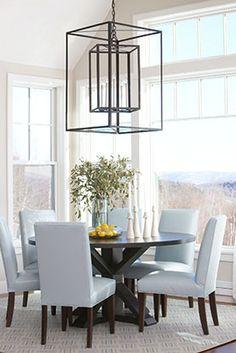 Light blue dining room chairs, round dining table, large windows, pendant lighting   Rachel Reider