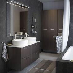 Harmaa kylpyhuone, jonka mustanruskeissa seinäkaapeissa kromatut vetimet.