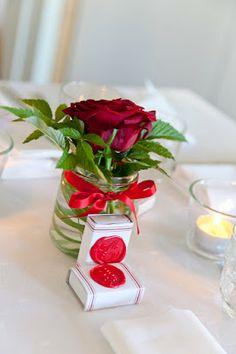 Bordsdekorationer: mindre burkar för tuikkun och större för blommorna. Ljusrött satinband runt.