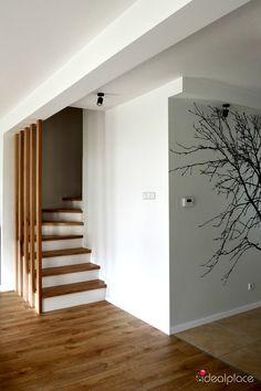 Fototapeta winylowa z motywem drzew. Schody z balustradą z tralkami do sufitu. Motyw drzew pojawia się w kilku pomieszczeniach domu. Remont i wyposażenie - projekt Ideal Place.