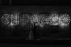 Artistic black and white night portrait of bride and groom under Chicago sign in courtyard of Salvage One by local wedding photographer Emma Mullins Photography.