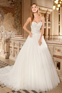 266 This strapless, soft tulle ball gown features a sweetheart neckline and ruched tulle sash with beaded applique on the natural waist. The bodice is embellished with decadent beaded embroidery and crystal accents. The tulle skirt flows into a chapel length train.