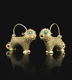pair of lion-form gold earrings, Persia, 12th century each composed of gold, hammered and chased, designed as stylised lions decorated with twisted wire and inset green and turquoise stone eyes Quantity: 2 2.5cm. height. 3.5cm. width.