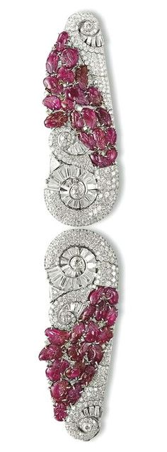 AN UNUSUAL ART DECO RUBY AND DIAMOND BRACELET PAIR OF DOUBLE-CLIPS - Designed as two matching tapered panels, each decorated with old, brilliant and baguette-cut diamond scrolls accented by a carved ruby cluster of foliate motif, detaching to form two clips, mounted in platinum, circa 1935