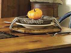 Set your fall table with old wood bread plates and vintage pie tins, and wrap them up with homespun fabric strips or ribbon. Top it all off with a miniature pumpkin for harvest charm. To see more of this photo and find out more about the items shown, turn to page 68 of our September 2014 issue or page 3 of our online Craft Fair, www.countrysampler.com/craftfair