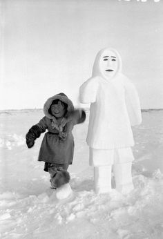 Theresie, three-year-old daughter of Erkuaktok [Iquugaqtuq], a Pelly Bay [Arvilikjuaq] Inuk, standing next to a snowman carved by her father. 1951.  Credit: Richard Harrington