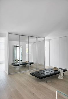 Elegant and modern wardrobe closet with mirrored sliding doors and a practical chaise by Poul Kjaerholm.
