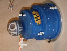 """Star Wars Cake - Star Wars cake for a little boy's birthday.  I really wanted to do it black, but the mom didn't want black (can't say I blame her - but it sure would have looked good).  Butter cake with BC icing.  Death star is a styrofoam ball covered in fondant; star fighter planes also fondant/gumpaste, lego figures.  Dusted with disco dust, but didn't look """"starry"""" enough, so I piped on the BC stars."""
