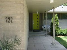 The slim, brushed-metal house numbers and the original front door sporting a tidy column of square windows against a jaunty lime-green backdrop are the first clues to the nhome's mid-century pedigree. Mid Century Modern Door, Mid Century Exterior, Mid Century House, Metal House Numbers, Square Windows, Modern Ranch, Front Door Colors, Exterior Makeover, House Entrance