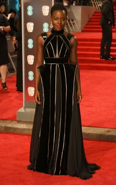 "Lupita Nyong'o at the BAFTAs 2018 The ""Black Panther"" actress donned a black-and-gold Elie Saab number. [Photo: Getty]"