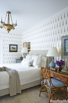 """Going for """"calm, clean, ethnic chic,"""" Turner mixed two Muriel Brandolini fabrics with muted metallic prints for the guest bedroom's walls and bed. The bedding — Leontine Linens — is implemented once more.    - HouseBeautiful.com"""