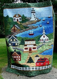 Gorgeous landscape quilt of a lake with lighthouse and nearby town. Amazing work.
