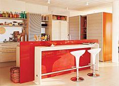 Um painel vermelho separa a bancada da mesa do balcão de refeições