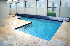 A low wall covered in multicolored Italian glass tiles forms a striking backdrop for this pool.