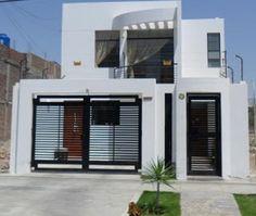 Fachada de casa angosta de dos niveles en color blanco
