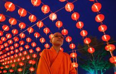 A Buddhist monk walks under decorations at a temple in Nonthaburi, Thailand.  Photograph: Chaiwat Subprasom/Reuters