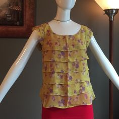 American Eagle blouse This is the cutest mustard colored blouse. It's a yellow color with red and purple-ish flowers. It's layered in the front and sheer. I have a red cami underneath it!! American Eagle Outfitters Tops Blouses