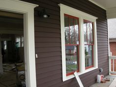 "cedar siding ""Turkish coffee"" brown, trim creamy white, windows ""Roycroft"" red."