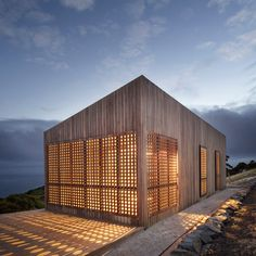 Moonlight Cabin, a modest, modern Australian vacation home is designed to partially shut down as required when not in use and during harsh weather with perforated timber shutters of local timber. By Jackson Clements Burrows Architects.