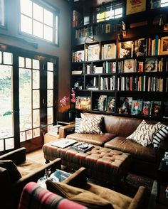 Bookshelf: A leather couch and a tufted ottoman in a room with black built-in shelving.