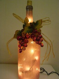 lighted wine bottle with grapes and raffia