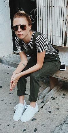 Olive overalls and a striped shirt paired with white sneakers