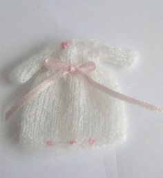 Hand knitted girls dress in soft white wool with pink ribbon and decoration