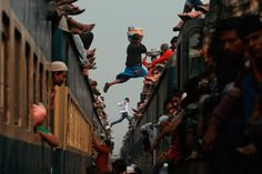 In the outskirts of Dhaka, Bangladesh, a vendor jumps from the top of one overcrowded train to another as thousands of Bangladeshi Muslims try to return home. Pictures Of The Week, Free Pictures, Perfectly Timed Photos, Meanwhile In, Sports Pictures, India Travel, Photojournalism, Incredible India, Portrait